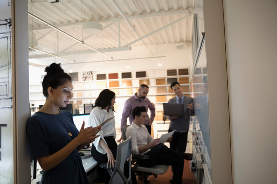 Designers brainstorming, meeting at whiteboard in creative office