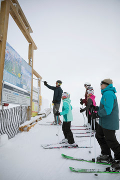 Family skiers looking at ski resort map