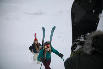 Female skier friends hiking up snow covered hill