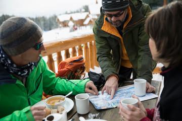 Mature friend skiers enjoying breakfast, preparing with map on ski resort balcony