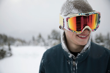 Smiling male snow covered skier wearing goggles