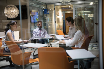 Business people planning, reviewing paperwork in office meeting