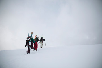Female skier and snowboarder friends hiking up snow covered hill
