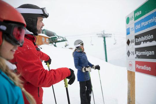 Family snowshoeing, looking at ski resort map