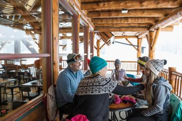 Family skiers eating apres-ski on ski resort lodge balcony
