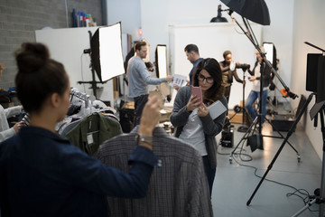 Wardrobe stylists photographing clothing for photo shoot in studio