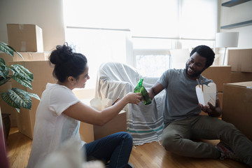 Young couple taking a break from packing, toasting beer bottles and eating Chinese takeout Food