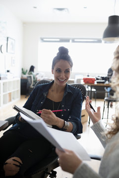 Smiling female designer with paperwork listening to colleague in office