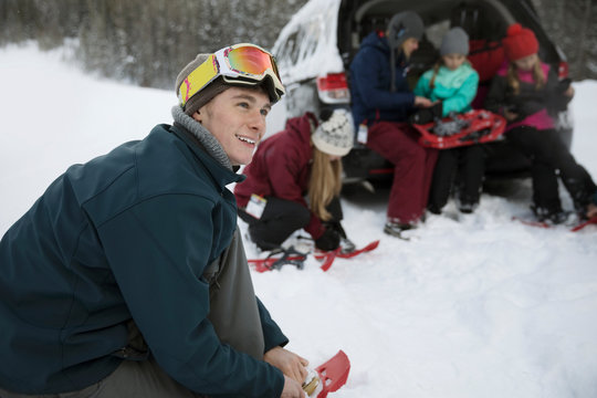 Smiling young man putting on snowshoes with family at car in snow