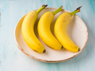 Three bananas on a plate on green turquoise background. Healthy lifestyle concept