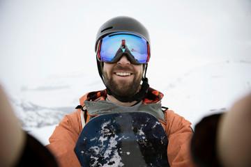 Selfie portrait smiling, confident male snowboarder