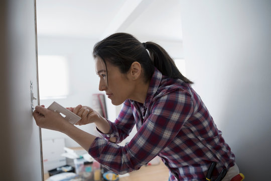 Woman installing eco-friendly light switch, DIY
