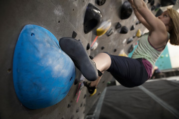 Determined, tough female rock climber climbing wall in climbing gym