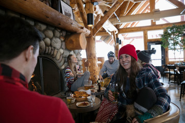 Friends enjoying apres-ski, drinking beer and hanging out at fireside in ski resort lodge