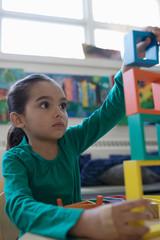 Focused preschool girl stacking building blocks