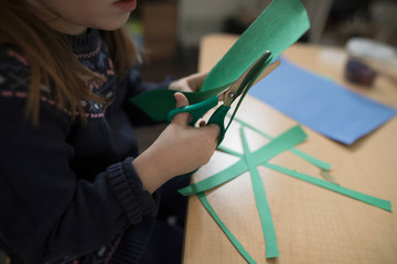 Preschool girl cutting construction paper for art and craft project in classroom