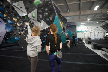 Female instructor guiding girl rock climbing student at climbing wall in climbing gym