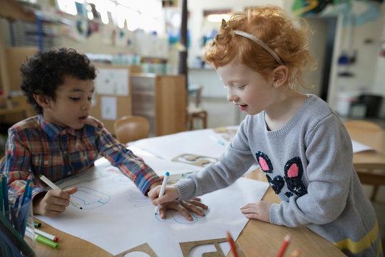 Preschool girl tracing boy