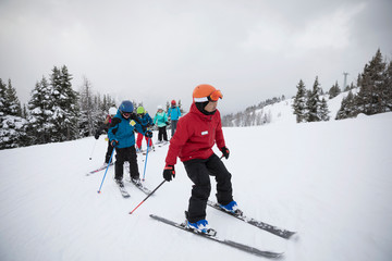 Instructor leading ski lesson for kids in snow