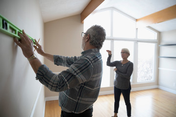 Senior couple using level tool on wall, preparing for remodel, DIY