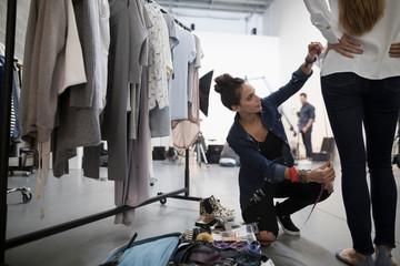 Female wardrobe stylist measuring model for photo shoot in studio