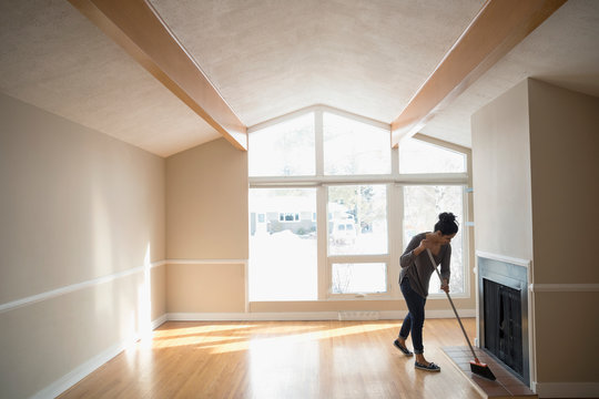 Young woman moving out, sweeping empty living room