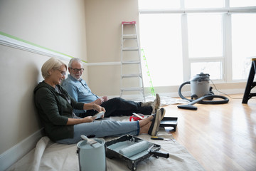 Senior couple preparing to paint in living room, looking at paint swatches, DIY