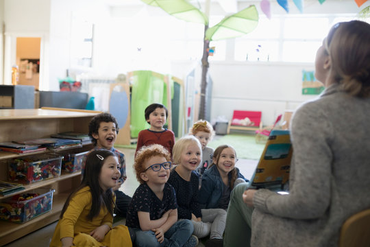 Preschool students listening to teacher reading book during story time in classroom