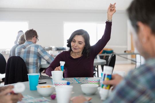 Senior woman playing bingo, winning with arm raised in community center