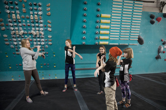 Female instructor and girl rock climber students stretching arms, preparing at climbing wall in climbing gym
