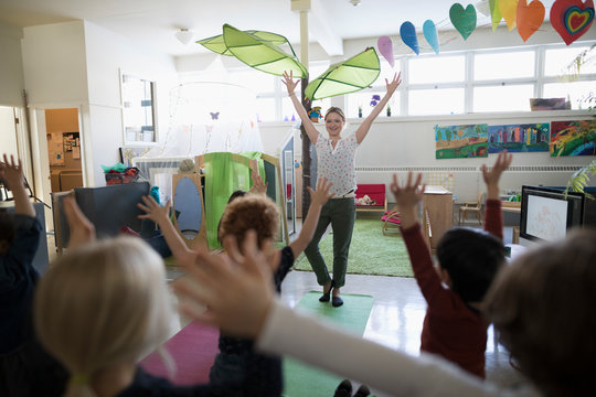Preschool teacher and students practicing yoga tree pose in classroom