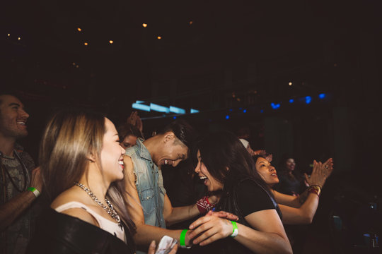 Happy, playful young millennial friends laughing and dancing at nightclub