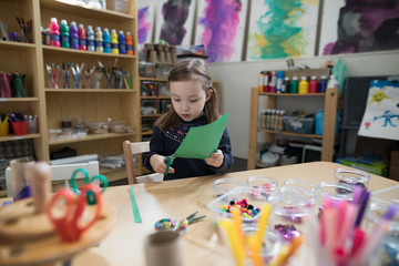 Preschool girl cutting construction paper for art and craft project in classroom Fotobehang