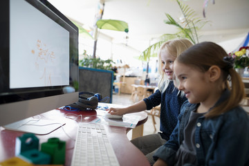 Smiling preschool girl students drawing at computer in classroom