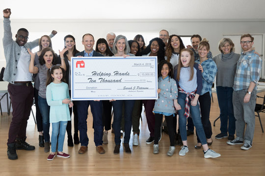 Portrait enthusiastic community with large donation check cheering in community center