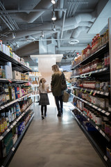Affectionate mother and daughter holding hands, grocery shopping in market aisle
