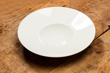 Plato blanco redondo hondo sobre mesa de madera rústica. Vista superior