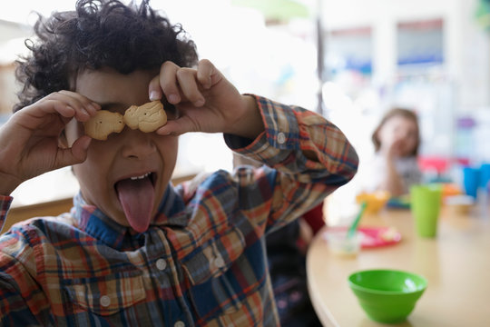 Portrait playful preschool boy covering eyes with animal crackers during snack time