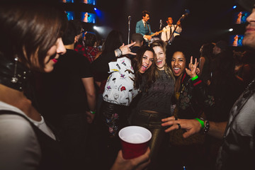 Portrait confident, playful millennial women dancing and partying in nightclub