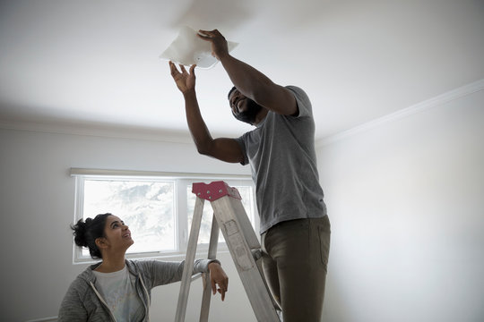 Young couple moving in, replacing light fixture, DIY