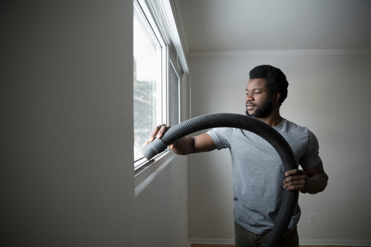 Young man moving out, cleaning and vacuuming window sill, DIY