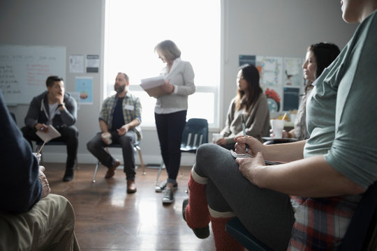 Woman leading support group discussion in circle in community center