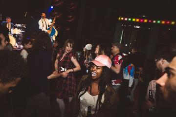 Enthusiastic young female milennials dancing, enjoying music concert in nightclub Fotobehang