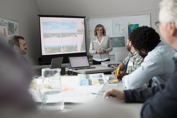 Smiling female city planner leading presentation in office