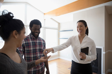 Happy young couple buying new house, receiving keys from realtor