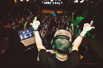 Enthusiastic DJ on stage gesturing to crowd in nightclub