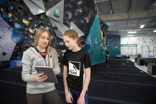 Female instructor and girl rock climbing student using digital tablet at climbing wall in climbing gym