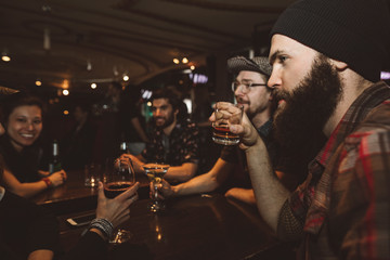 Male millennial hipster drinking whiskey in bar, listening to friends