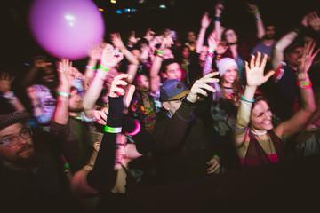 Milennials dancing, cheering at music concert in nightclub Fotobehang