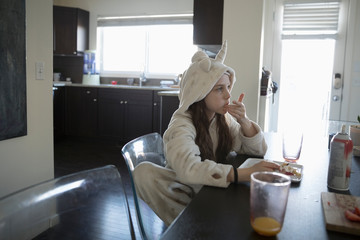 Girl in unicorn pajamas eating breakfast at dining table
